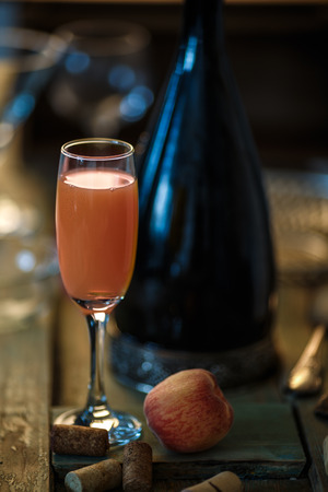 bellini: Famous Italian Bellini alcoholic cocktail made from pink peach puree with prosecco. Official IBA cocktail. Natural lighting, rustic styled, very narrow depth of field, selective focus