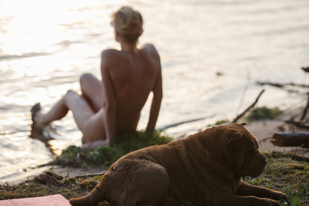 guarding: Rear view of slim woman siitng on the river bank with her dog (shar pei) guarding her. Focus on the dog. Vacation,relaxation concept Stock Photo