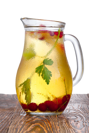 enriched: Glass pitcher of homemade spritzer (schorle) enriched with cherries and apple slices. Jug full of non-alcoholic sparkling and cold carbonated juice. Stock Photo
