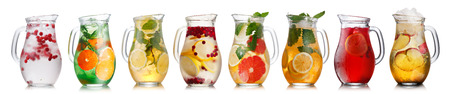Collection of different drinks in glass pitchers. Jugs full of spritzers, schorle,lemonade,iced tea, detox waters.