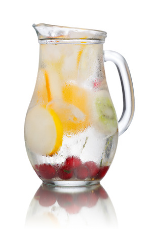 misted: Glass pitcher of homemade detox water enriched with cherries and frozen fruit wedges. Misted jug full of cold water with popsicles. Clean eating Stock Photo