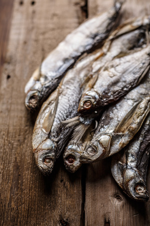 narrow depth of field: Dried fish on wooden table. Selective focus, narrow depth of field.