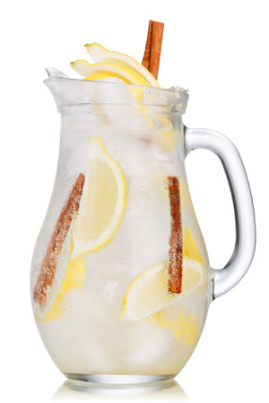 carbonated: Jug of lemon cinnamon sparkling lemonade (spritzer). Carbonated iced water with lemon and cinnamon sticks in a glass pitcher