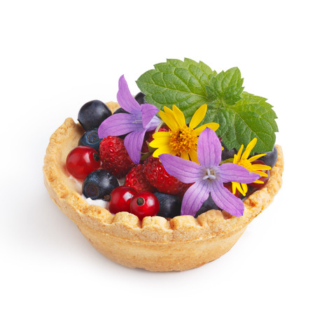 sweet tart: Dessert with wild berries decorated with mint leaves and wildflowers. Sweet tart with wild strawberry, blueberry and red currant. Large DOF