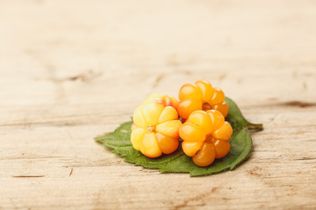 chicout�: Cloudberries (moroshka) on a wooden table. Wild northern berry. Shallow depth of field