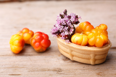 chicout�: Cloudberry tart decorated with wild marjoram. Sweet baked dessert with fresh wild cloudberries on a wooden table.
