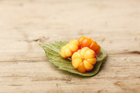 chicouté: Cloudberries (moroshka) on a wooden table. Wild northern berry. Shallow depth of field