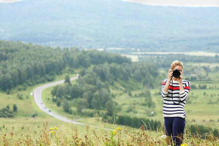 adventurous: Adventurous female photographer taking a picture of mountains standing on a hilltop facing the camera Stock Photo
