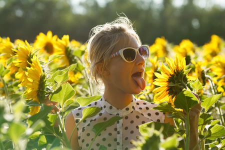 frolicking: Eccentric woman wearing sunglasses, black and white polka dot dress fooling around in the sunflower field showing her tongue. Selective focus,natural light, backlit,flare