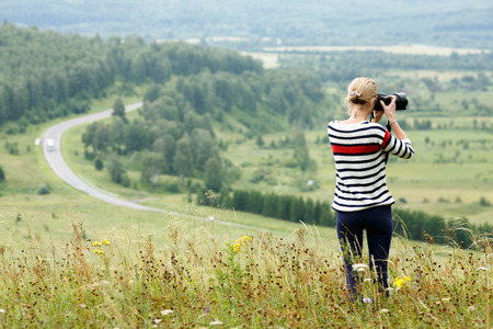 adventurous: Adventurous female photographer taking a picture of mountains standing on a hilltop Stock Photo