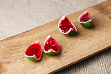 jello: Watermelon like tequila  jelly (jello) shots made out of carved lime on wooden plank. Unusual adult party drinks
