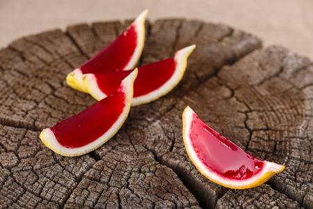 jello: Lemon tequila strawberry jelly (jello) shots on a old wooden wheel. Unusual adult party drinks Stock Photo