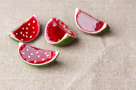 jello: Watermelon like tequila  jelly (jello) shots made out of carved lime on linen tablecloth. Unusual adult party drinks