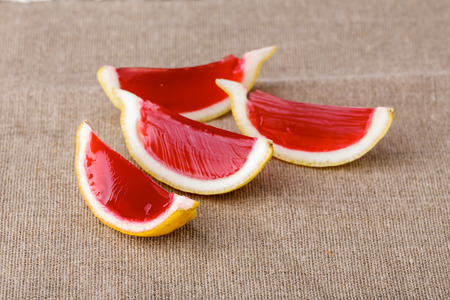 clothed: Lemon tequila strawberry jelly (jello) shots on a linen clothed table. Unusual adult party drinks