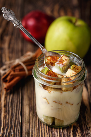 stick of cinnamon: Parfait-style healthy layered snack or dessert with yogurt and apple with ground cinnamon in  glass on wooden table.