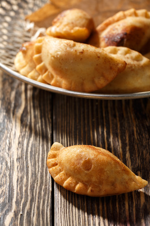 Fried colombian empanadas on wooden table. Savory stuffed patties also known as pastel,pate or pirozhki