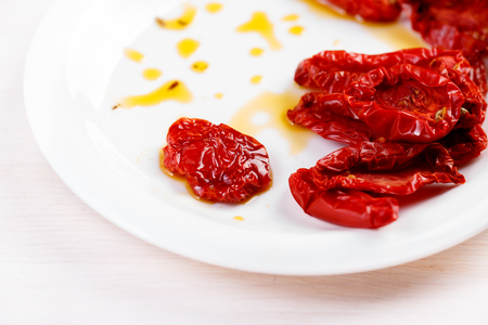 sun dried: Sun dried tomatoes with olive oil on white plate