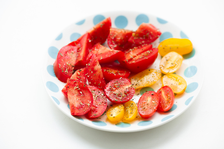 r sliced: Chopped tomatoes on a polka dot plate Stock Photo