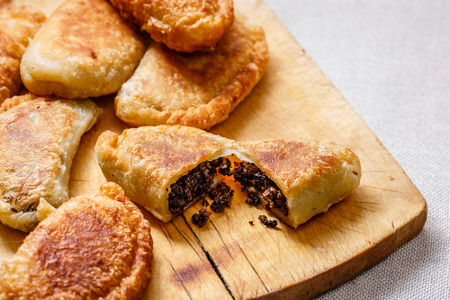 sized: Colombian empanadas (snack sized savory patties) on wooden board. Latin cuisine Stock Photo