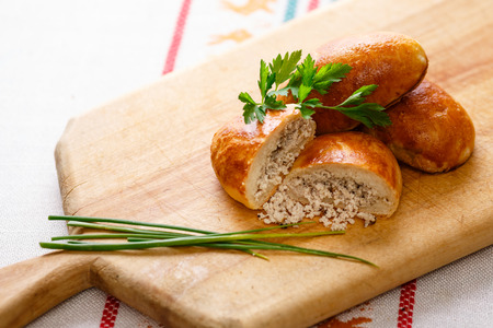 pastes: Russian pirozhki (baked patties) on wooden cutboard