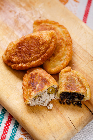 pastes: Colombian empanadas (snack sized savory patties) on wooden board. Latin cuisine Stock Photo