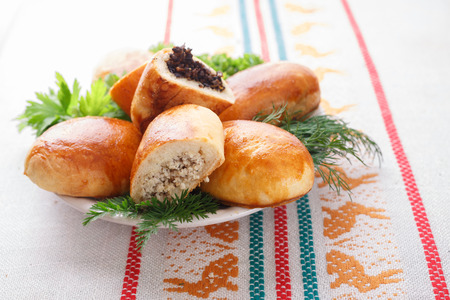 Russian pirozhki (baked patties) on wooden cutboard
