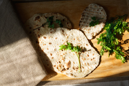 naan: Indian naan bread on wooden table next to greens
