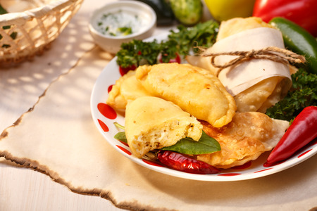 resemble: Cheese empanadas (savory patties) on wooden table. Selective focus, lit to resemble direct sunlight Stock Photo