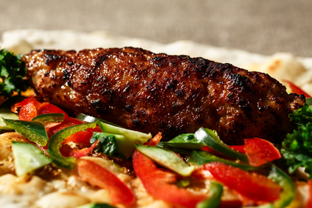 Shish kofte (kofta kebab) with vegetables and herbs on naan or lavash or pita flatbread