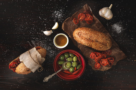 burnished: Ingredients for whole grain sandwich with sun dried tomatoes, olives and garlic on dark burnished wooden table. Top view, low key image