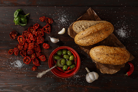 tomato: Ingredients for whole grain sandwich with sun dried tomatoes, olives and garlic on dark burnished wooden table. Top view