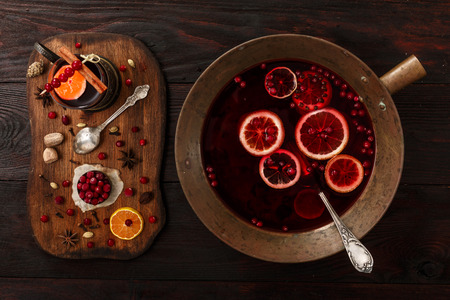 hot: Cranberry citrus punch or mulled wine with ingredients over dark wooden table.
