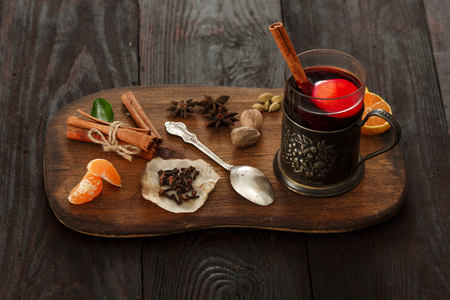 mulled wine spice: Glass of mulled wine (punch) in glass-holder served on wooden plate with spices over dark wooden table