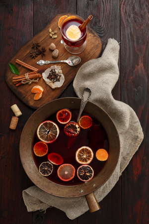 mulled wine spice: Brass bowl full of mulled wine (punch) next to glass of mulled wine served on wooden plate with spices over dark wooden table. Top view