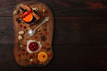 Cranberry citrus punch or mulled wine with ingredients over dark wooden table.