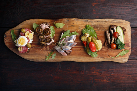 Variety of open sandwiches of buttered dense, dark rye bread with different toppings. Danish smorrebrods on wooden backdrop. Northern cuisine Zdjęcie Seryjne