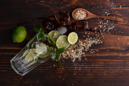 highball: Mojito in faceted highball with its ingredients on dark wooden table. Stock Photo