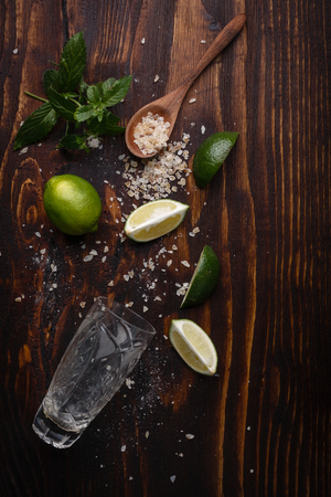 highball: Ingredients for mojito on dark wooden table. Lime, rough cane sugar,mint and highball