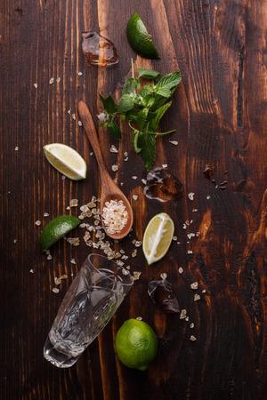 Zutaten für Mojito auf dunklen Holztisch. Kalk, Löffel aus groben Rohrzucker, Minze, Eiswürfel und Highball Standard-Bild