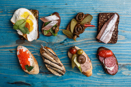 Variety of open sandwiches from wholegrain baguette and rye bread with different toppings over aged blue wooden backdrop.