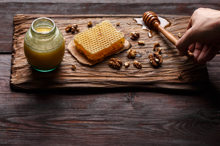 burnished: Honey dip,glass jar, honeycomb and walnuts on carved wooden serving plate over burnished wood table. Selective focus