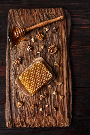 burnished: Honey dip, honeycomb and walnuts on carved wooden serving plate over burnished wood table. Top view, close up