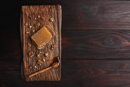 burnished: Honey dip, honeycomb and walnuts on carved wooden serving plate over burnished wood table. Top view, copy space