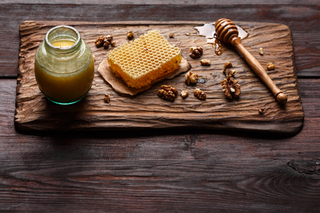 burnished: Honey dip, honeycomb and walnuts on carved wooden serving plate over burnished wood table. Copy space,selective focus