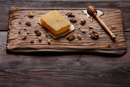 burnished: Honey dip, honeycomb and walnuts on carved wooden serving plate over burnished wood table. Angle view, copy space,selective focus