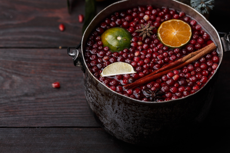 burnished: Cranberry mandarin pomegranate punch or mulled wine in a rustic aged pot near blue spruce branch Stock Photo