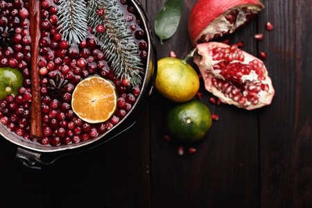 Cranberry mandarin pomegranate punch or mulled wine in a rustic aged pot over wooden backdrop Stock Photo