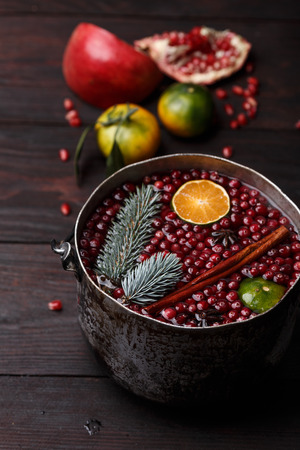 burnished: Cranberry mandarin pomegranate punch or mulled wine in a rustic aged pot over wooden backdrop Stock Photo