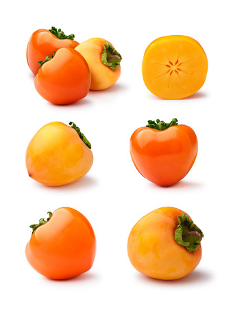 Set of whole and halved Hachiya persimmons (fruits of Diospyros kaki) isolated on white. Gloss, matt, scuffed appearance, infinite depth of field Stock Photo