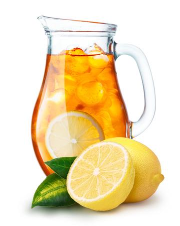 limonada: Té helado en una jarra. Jarra llena de té helado o limonada con los limones en primer plano